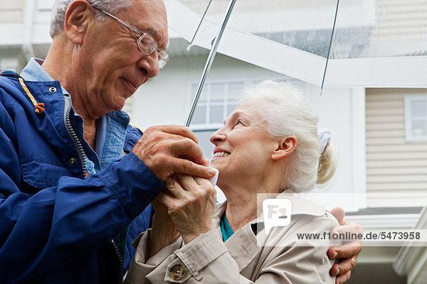 Seniorenpaar mit Regenschirm im Freien