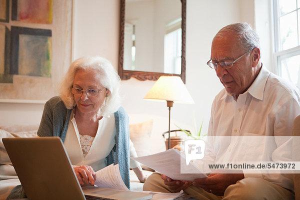 Seniorenpaar mit Latop zu Hause