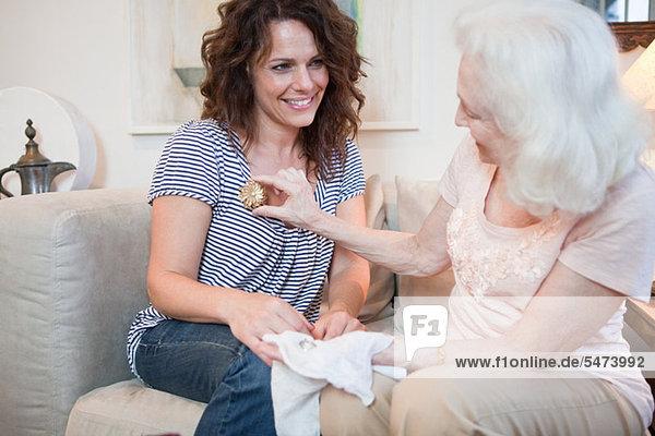 Senior Woman geben Tochter eine Brosche
