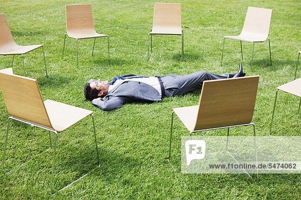 liegend liegen liegt liegendes liegender liegende daliegen Geschäftsmann Stuhl umgeben Gras
