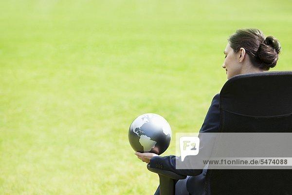Geschäftsfrau sitzt im Freien und hält einen Globus