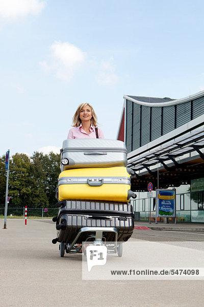 Mittlere erwachsene Frau schiebt Gepäckwagen zum Flughafen