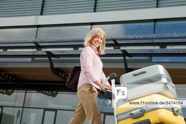 Frau mittleren Alters drängen Gepäckwagen zum Flughafen
