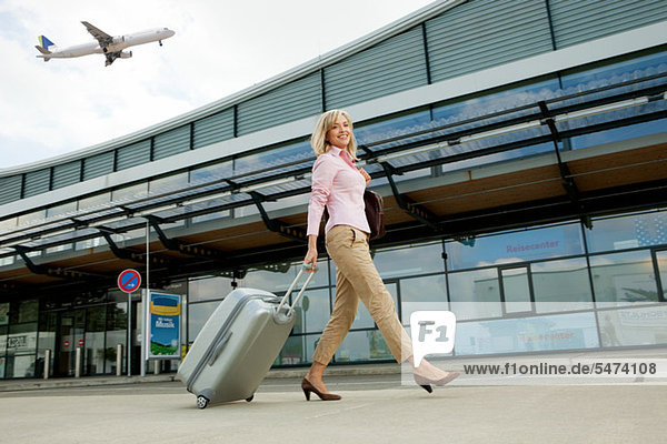 Mittlere erwachsene Frau mit Gepäck zum Flughafen