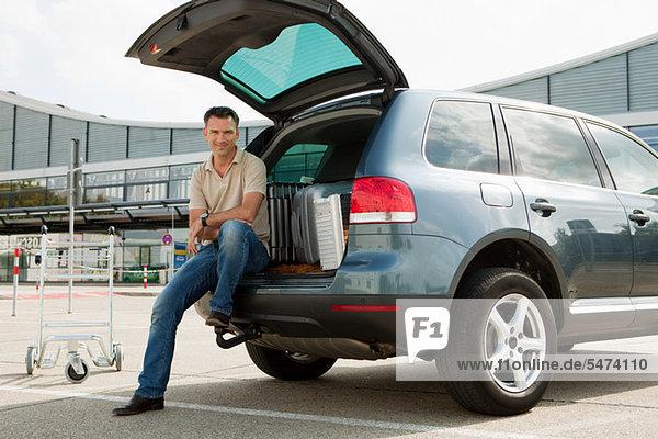 Mann sitzt auf dem Wagen auf dem Parkplatz des Flughafens
