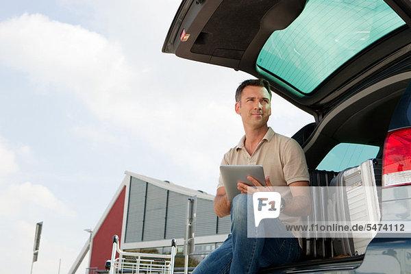 Mann mit Datentablett auf dem Flughafenparkplatz
