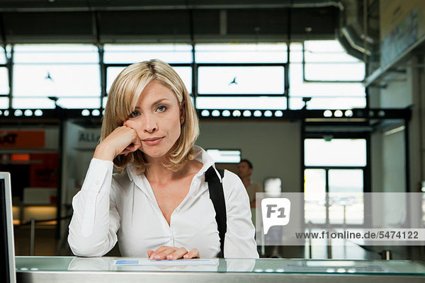 Gelangweilte Frau am Check-in-Schalter des Flughafens
