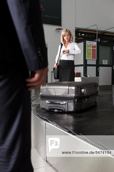 Mittlere erwachsene Geschäftsfrau  die auf das Gepäck im Flughafengepäck wartet.
