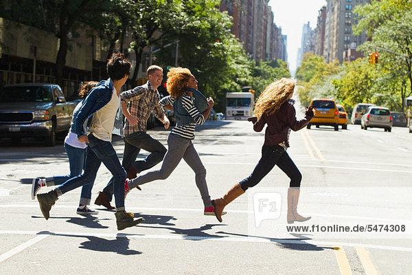 Fünf Freunde  die durch die Stadt rennen.