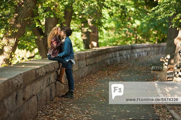 Junges Paar umarmt an der Wand im Park