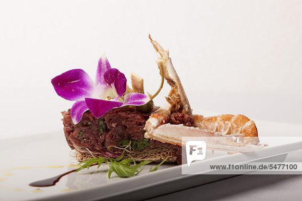 Charolais Rindfleisch Filet Tartar und gegrillte Langusten Schwanz mit Soja-Milch