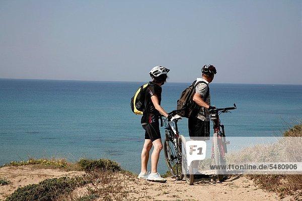 Couple ona mountain bikes by San Giovanni di Sinis beach on the Sinis peninsula  Sardinia  Italy