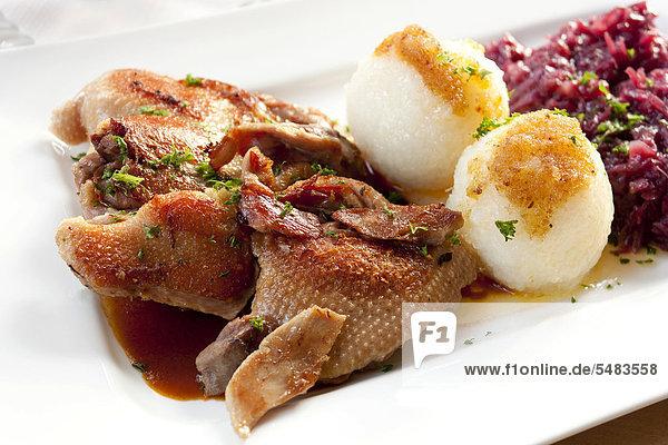 Eine halbe gebratene Ente mit Kartoffelklößen und Rotkohl