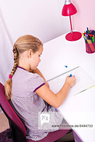 Junge Schülerin bei ihren Hausaufgaben am Schreibtisch