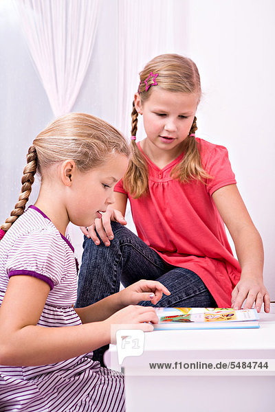 Zwei junge Schülerinnen sitzen am Schreibtisch und machen ihre Hausaufgaben