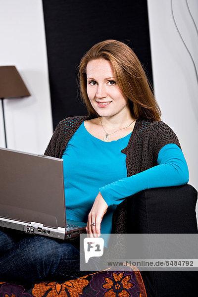Junge Frau mit einem Laptop im Wohnzimmer
