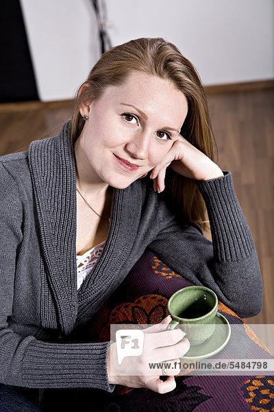 Eine junge Frau trinkt Kaffee im Wohnzimmer