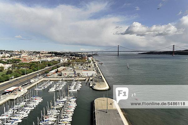 Brücke über den Fluss Tejo  Ponte 25 de Abril  eingeweiht 1966  Hängebrücke  vorne der Yachthafen  Alcantara  Lissabon  Portugal  Europa