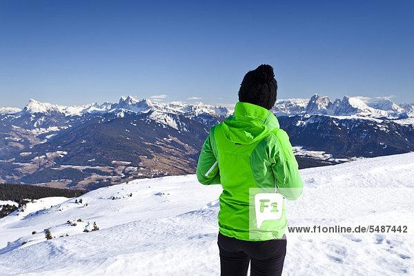 Bergsteigerin auf dem Rittnerhorn oberhalb vom Ritten  Bozner Umgebung  Blick in Richtung Dolomiten  Langkofel und Plattkofel  Geislerspitzen  Südtirol  Italien  Europa