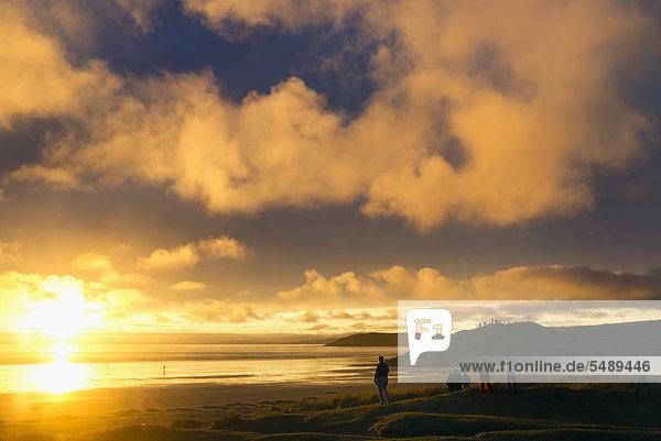 Menschen betrachten das Wolkenspiel über dem Atlantik  Sonnenuntergang  Finistere  Bretagne  Frankreich  Europa  ÖffentlicherGrund