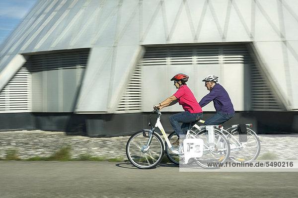 Deutschland  Bayern  Raisting  Seniorenpaar mit Elektrofahrrad in der Nähe des Radiosenders