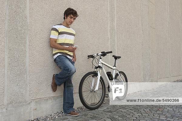 Junger Mann mit Telefon im Stehen auf dem Fahrrad