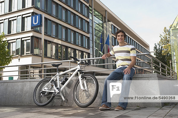 Young man with bicycle  smiling  portrait