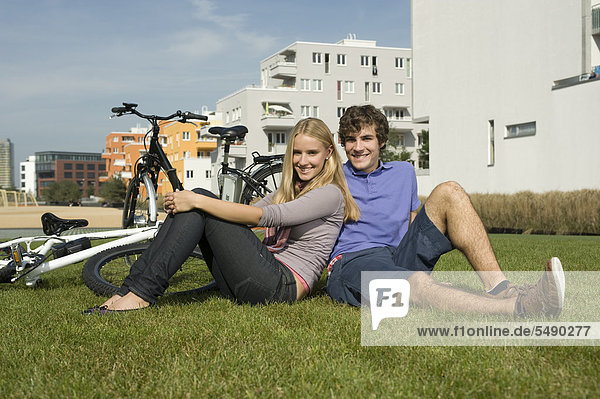 Germany, Bavaria, Couple sitting in grass, smiling, portrait RNF000721