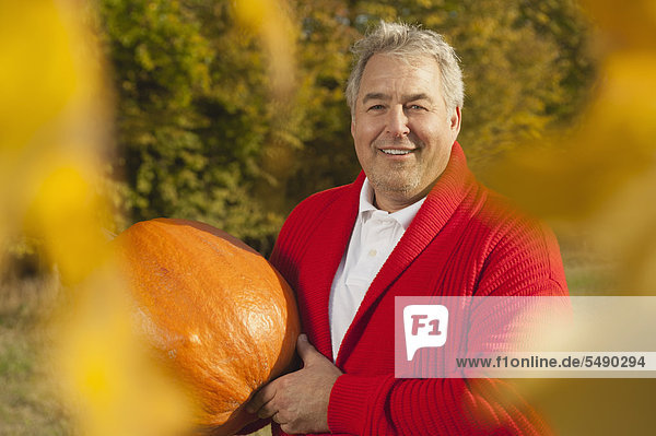 Mature man holding pumpkin  smiling  portrait