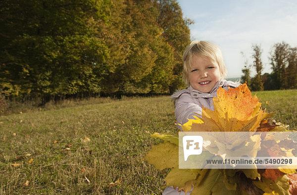 Girl holding leaves  smiling  portrait