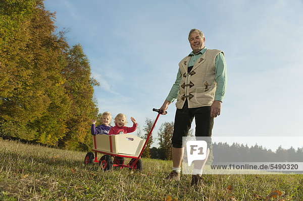 Deutschland  Bayern  Großvater zieht Enkelinnen im Wagen sitzend