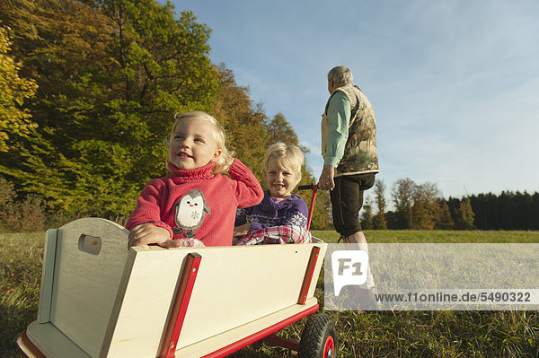 Germany  Bavaria  Grandfather pulling granddaughters sitting in wagon