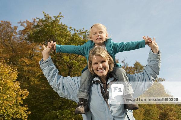 Germany  Bavaria  Mother carrying daughter on shoulder  smiling