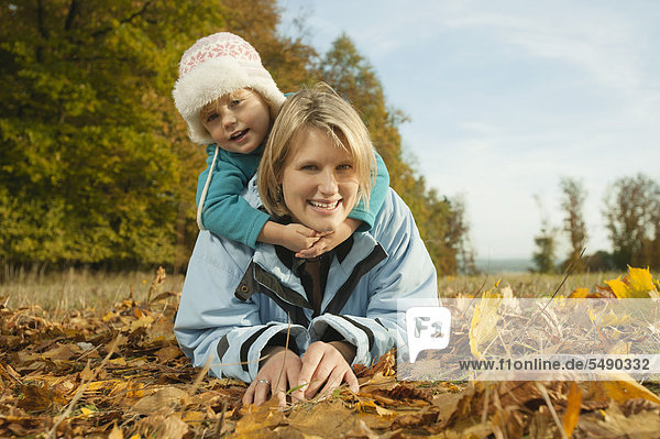 Germany  Bavaria  Mother and daughter lying on leaves during autumn  smiling  portrait
