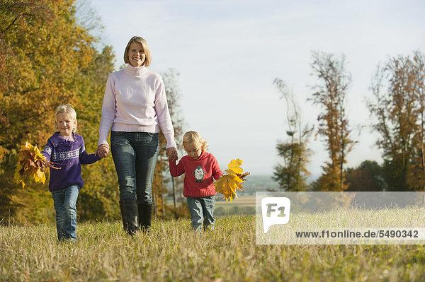 Deutschland  Bayern  Mutter und Töchter gehen auf der Wiese spazieren