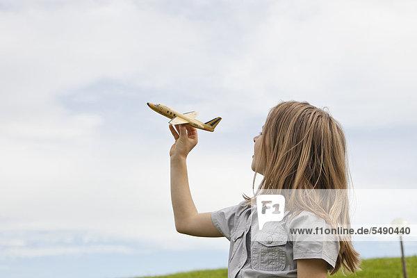 Mädchen spielt mit Modellflugzeug im Park