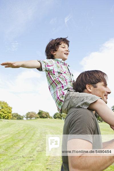 Deutschland  Bayern  Vater mit Sohn auf der Schulter im Park  lächelnd