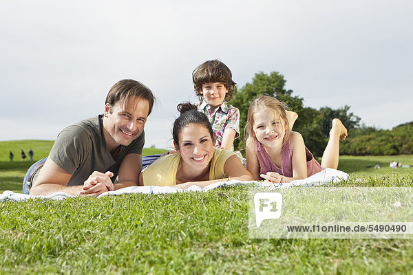 Deutschland  Bayern  Familie auf Decke im Park liegend  lächelnd  Portrait