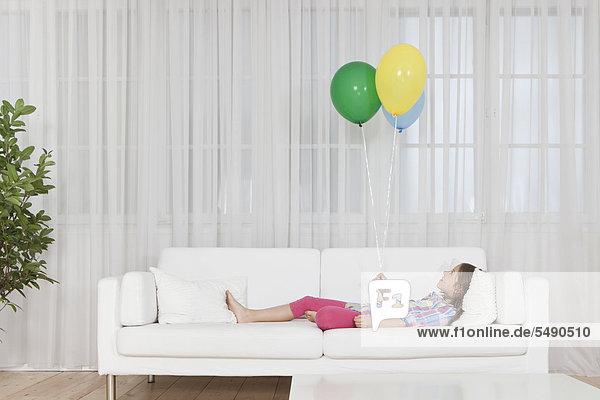 Mädchen auf der Couch liegend mit Ballon