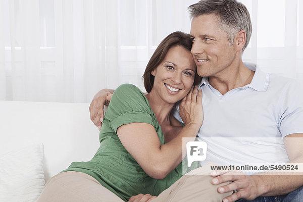Deutschland  München  Paar auf Couch sitzend  lächelnd