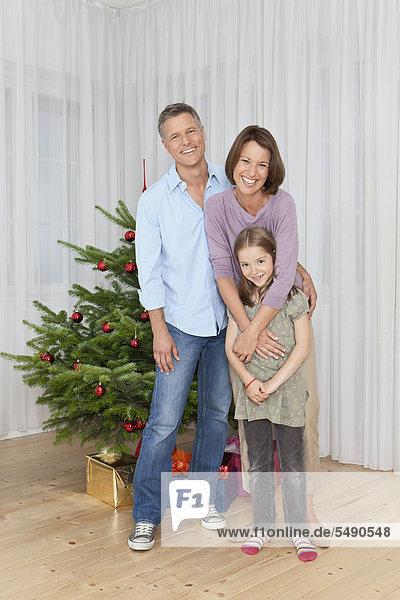 Deutschland  München  Familie steht am Weihnachtsbaum  lächelnd  Portrait
