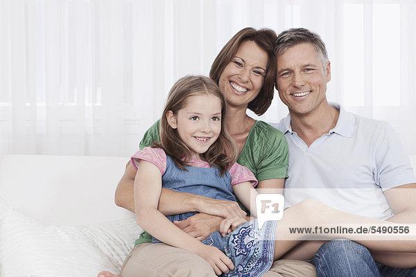 Deutschland  München  Familie auf Couch sitzend  lächelnd