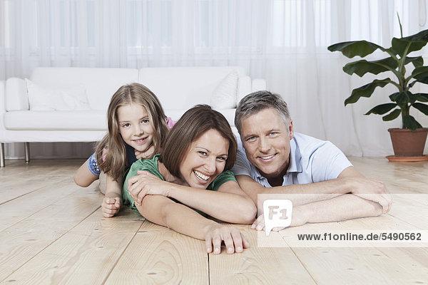 Deutschland  München  Familie auf dem Boden liegend  lächelnd  Portrait