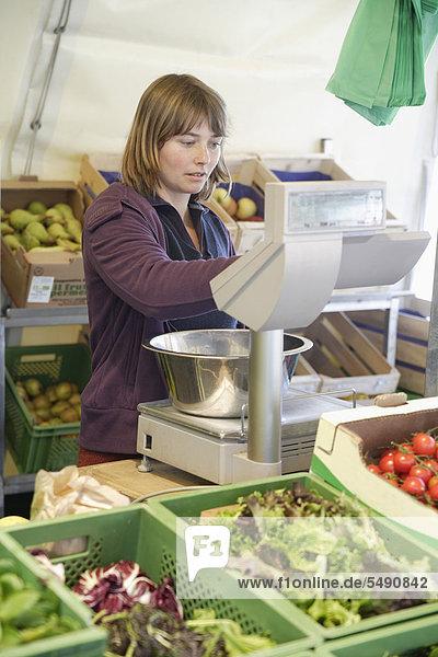 Deutschland  Oberbayern  Wolfratshausen  Junge Frau  die Gemüse vom Markt kauft