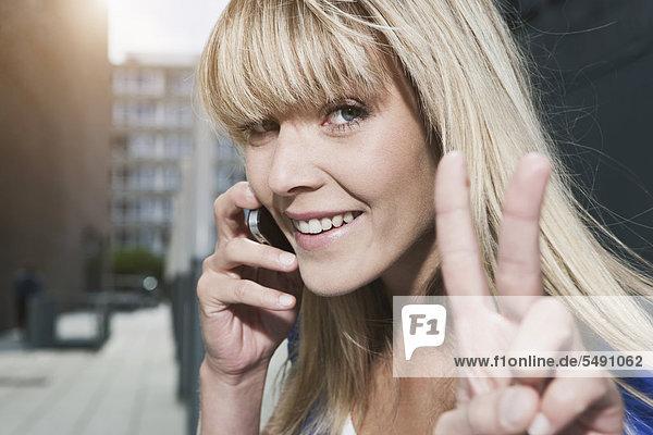 Junge Frau mit Handy  lächelnd  Portrait