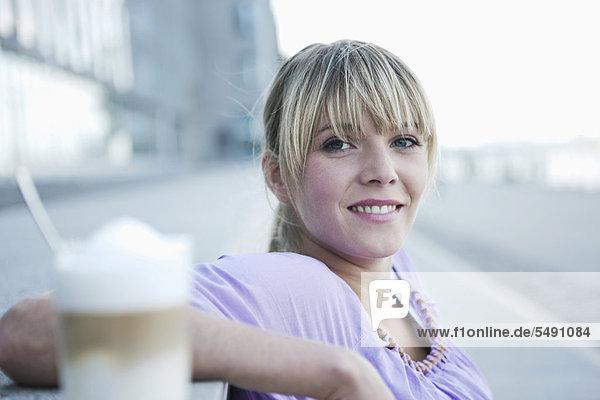 Junge Frau lächelt mit Kaffee im Vordergrund