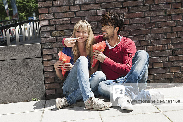 Germany  Cologne  Young couple eating french fries  smiling