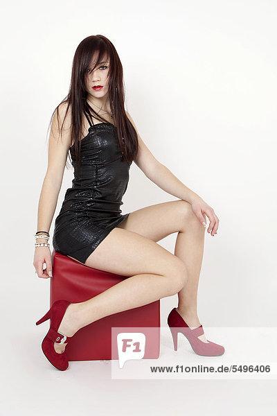 Junge Frau in schwarzem Lackkleid und High Heels posiert selbstbewusst auf rotem Sitzwürfel