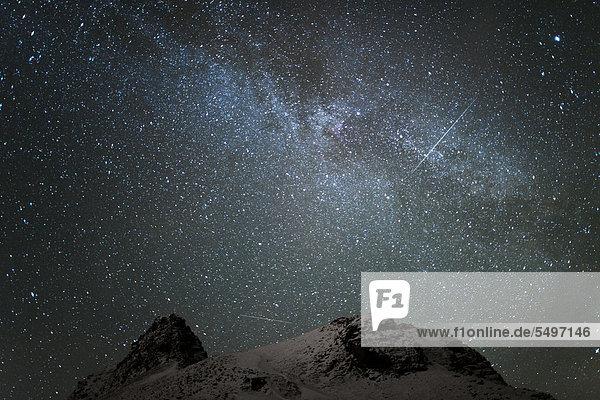 Die Milchstraße und zwei Spuren von Satelliten am winterlichen Sternenhimmel  die grünliche Färbung des unteren Himmelsbereiches enstammt sehr schwachem Polarlicht  Longyearbyen  Spitzbergen  Svalbard  Norwegen  Europa