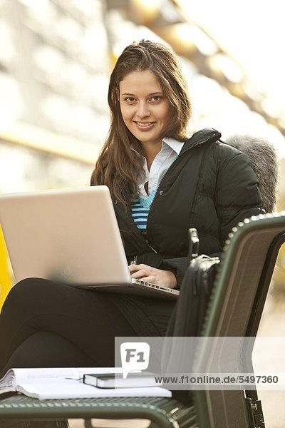 Studentin mit Laptop auf einer Bank